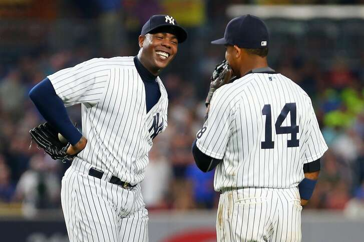 NEW YORK, NY - JULY 22: Aroldis Chapman #54 of the New York Yankees shares a laugh with Starlin Castro #14 during the ninth inning against the San Francisco Giants at Yankee Stadium on July 22, 2016 in the Bronx borough of New York City.  (Photo by Mike Stobe/Getty Images)