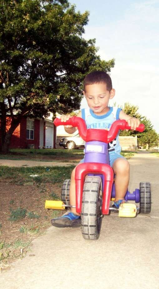 Juan Aranda, 2-year-old son of Juan Aranda and April Ochoa of Plainview, rides his tricycle on Saturday evening. Although storm clouds brew in the background, no rain had fallen in town by press time Saturday night. The forecast calls for a 20 percent chance of thunderstorms this afternoon with highs around 101. Tuesday sees another 20 percent chance of thunderstorms. Highs all week should be in the mid to upper 90s.