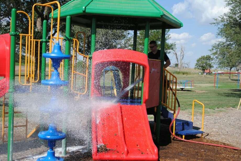 Plainview firefighter Ryan Collier sprays down a playground deck at Frisco Park on Tuesday afternoon after an unknown person attempted to set fire to the plastic and metal equipment. Photo: Ryan Crowe/Plainview Herald