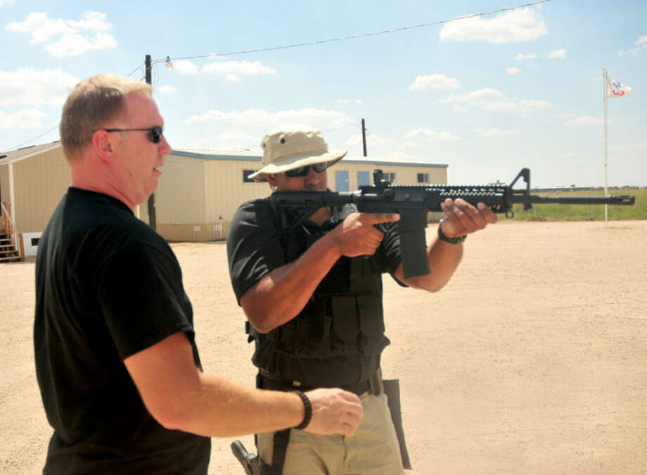 NATC instructor Kevin Macrae (above) helps student Zeke Burns set his sights during training at the bodyguard school just north of Tulia. At right, lead instructor Jon Tripps goes over the basics of gun safety during a classroom session on Friday. Photo: Homer Marquez/Plainview Herald