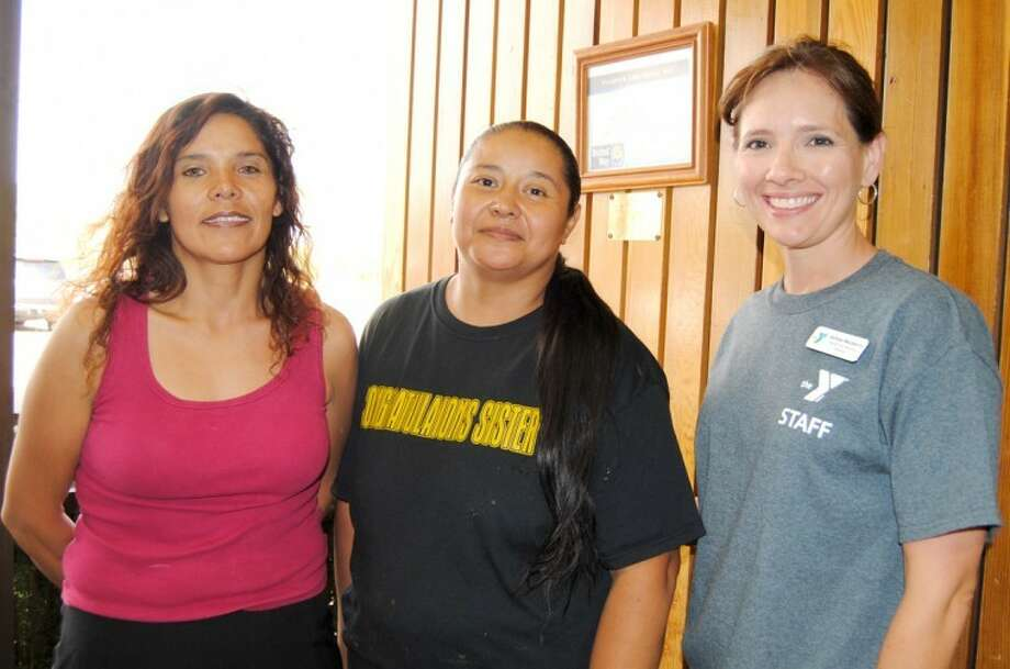 Doug McDonough/Plainview HeraldMatilde Ferrer Mariscal (left) and Elsa Ferrer-Hernandez, representing the Bloated Whales, are congratulated by YMCA Health and Wellness Director Ashley Mayberry during Friday's Pounds Off Plain view awards program. The Bloated Whales, which includes Stephanie Ferrer, Amber Ferrer and Juan Mariscal Jr., took first place by losing 10.9 percent of their body weight in eight weeks.