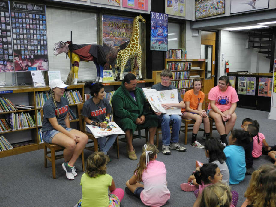 Junior Literacy Council members join community reader Rick Garcia Thursday night to read three books to children. Pictured are Hannah Smith (left), Monique Lucio, Rick Garcia, Parker Adamson, Shalin Lawson and Shayla Ross. Photo: Gail M. Williams | Plainview Herald