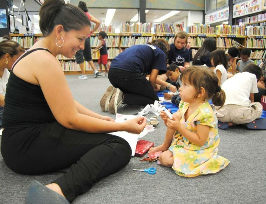 Doug McDonough/Plainview HeraldClaudia Jaquez helps her daughter, Amber, 3, make a paper sack puppet Monday during Unger Memorial Library's summer reading program. Held 10-10:45 a.m. Monday through Friday during June, the Texas Reading Club and Read-to-Me Club offer a variety of activities to encourage reading. The Read-to-Me Club is for children 4 to 7 years old while the Texas Reading Club is for rising third graders and older. Today's program will feature musician Andy Mason, with photography on Wednesday, healthy snacks on Thursday and horses on Friday.