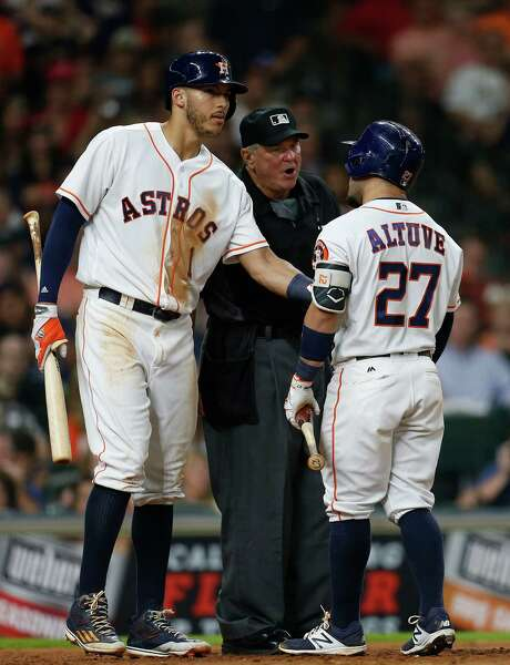 Carlos Correa, left, tries to separate Jose Altuve from plate umpire Dana DeMuth after Altuve was called out on strikes in the eighth inning. Photo: Karen Warren, Staff / © 2016 Houston Chronicle