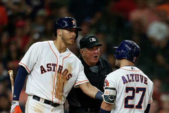 Carlos Correa, left, tries to separate Jose Altuve from home plate umpire Dana DeMuth after Altuve was called out on strikes in the eighth inning.