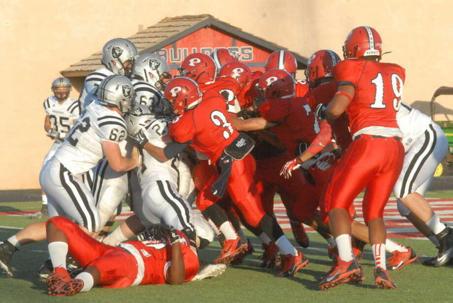 The Bulldogs' defense gangs up to stop a Raider runner during the first quarter Photo: Skip Leon/Plainview Herald