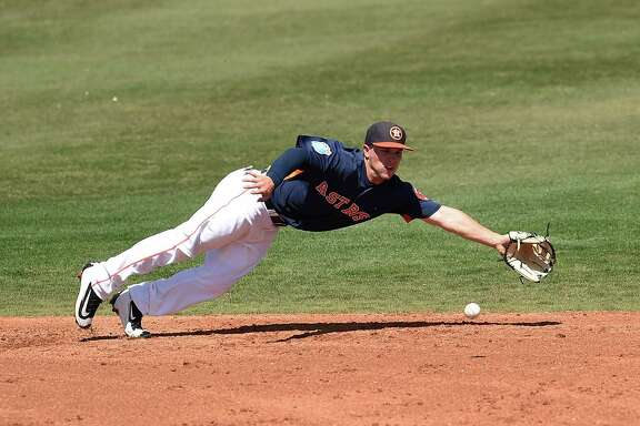 Alex Bregman f the Houston Astros dives for a ground ball during the third inning of a spring training game against the Washington Nationals at Osceola County Stadium on March 15, 2016 in Kissimmee, Florida.
