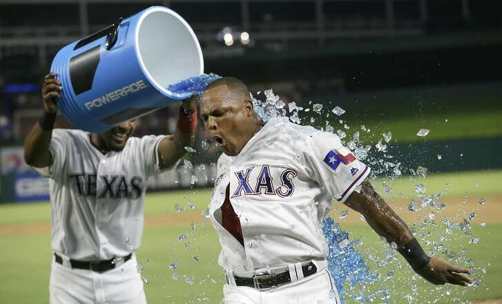 Texas Rangers Adrian Beltre, right, gets doused by teammate Elvis Andrus after Beltre hit a game winning two run homer during the ninth inning of a baseball game against the Oakland Athletics in Arlington, Texas, Monday, July 25, 2016. The Rangers won 7-6. (AP Photo/LM Otero)