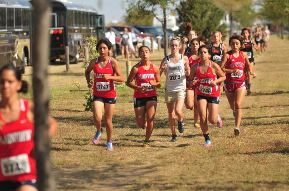 A group of four Lady Bulldog runners keep stride with a Tulia runner during the girls' three-mile race at the Plainview Invitational Saturday. The girls finished third in the meet. Photo: Homer Marquez/Plainview Herald