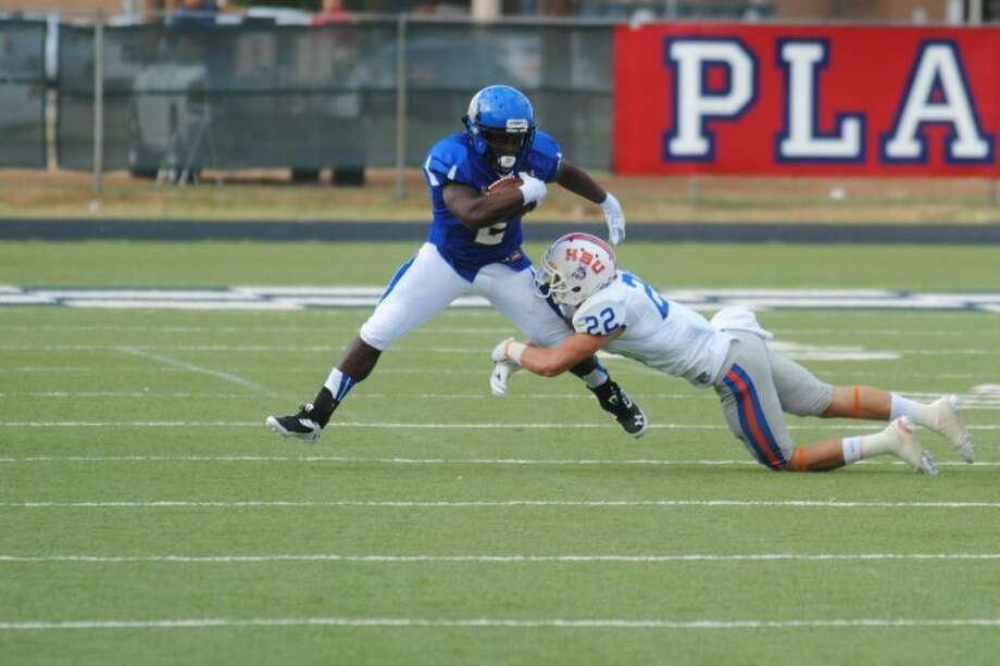Wayland Baptist University running back Kendall Roberson tries to break away from the tackle of Houston Baptist safety Cody Moncure during a college football game at Greg Sherwood Memorial Bulldog Stadium in Plainview Saturday night. Photo: Ryan Crowe/Plainview Herald