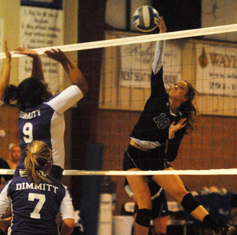 Plainview Christian Academy's Laura Beth Earhart (18) hits the ball past a Dimmitt blocker during a volleyball match at the PCA gym Tuesday. Photo: Skip Leon/Plainview Herald