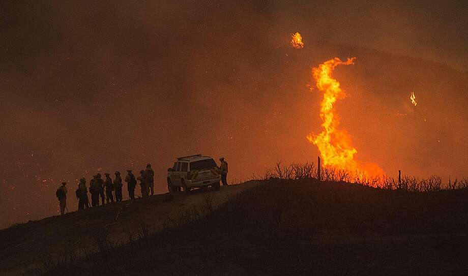 Firefighters battle the Soberanes Fire as it jumps a containment line in Carmel Highlands, Calif., on Monday, July 25, 2016. Ian Czirban, the head of Czirban Concrete Construction, was charged Friday with six felonies related to insurance fraud, submitting a false or forged document and tax evasion. His company was previously fined thousands in health and safety citations after the death of an employee battling the Soberanes Fire in 2016. Photo: Noah Berger, Special To The Chronicle