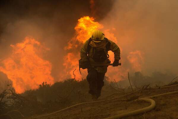 A firefighter battles the Soberane Fire as it jumps a containment line in Carmel Highlands, Calif., on Monday, July 25, 2016.