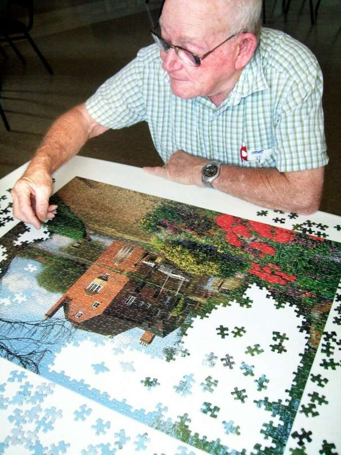 Billy Kennedy, a retired highway construction worker, looks to find the next puzzle piece this morning at the Hale County Senior Citizens Center. With today's high expected to reach 102 and highs the rest of the week forecast near the century mark, Kennedy and many others are spending most of their time indoors.
