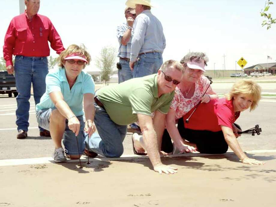 Brian McGann/Plainview HeraldCustomers and employees alike were invited to leave their mark Friday in the wet cement outside the new Great Plains Ag Credit offices on the I-27 east service road adjacent to Regional Park. The event was held during a customer appreciation day with many leaving their brands in the newly-poured sidewalk. Some even added handprints and footprints. Among those leaving their marks are Plainview GPAC employees Tammy Fields (left), Cliff Daniel, Daleyn Schwartz and Harriett Burleson.