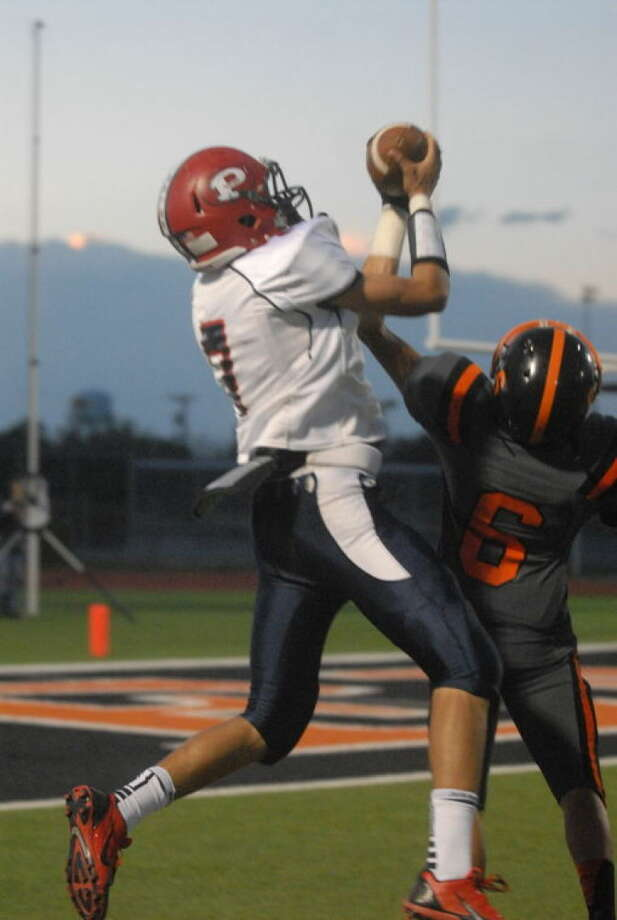 Keevon Crump leaps over Dumas's Cristian Landeros to catch a touchdown pass for Plainview in the first quarter of the Bulldogs' 42-14 victory in Dumas Friday night. Photo: Skip Leon/Plainview Herald