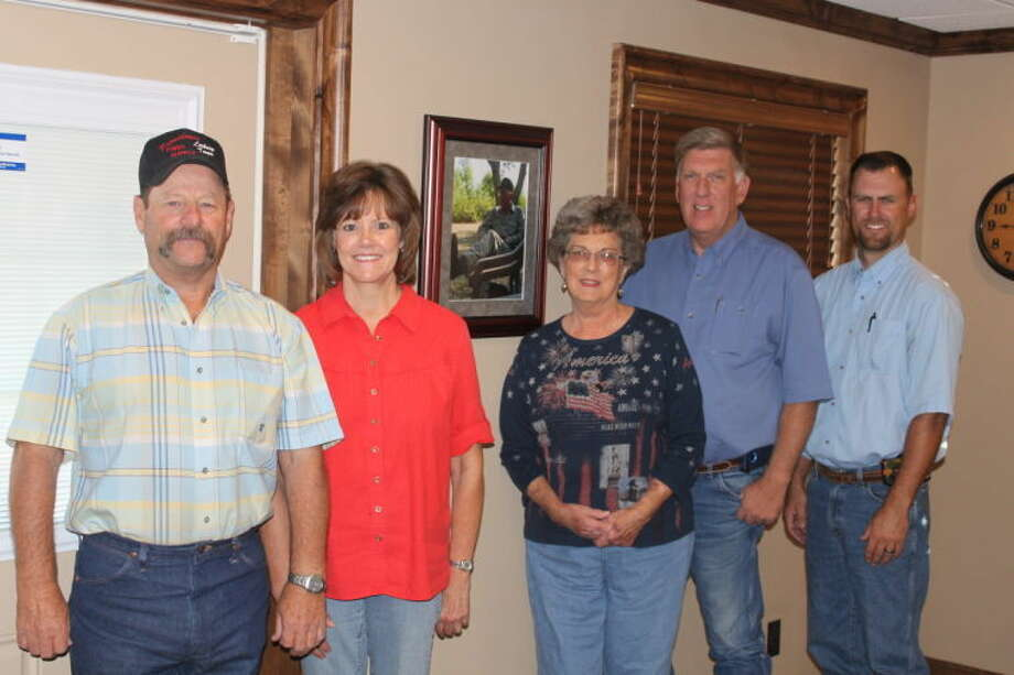 Standing inside the new office at Providence Farm Supply and in front of the picture of the late Warren Mathis are Glen Graves, manager; Robin Stoerner; Barbara Mathis, owner; Mike Mathis and Garrett Mathis. Photo: Courtesy Photo