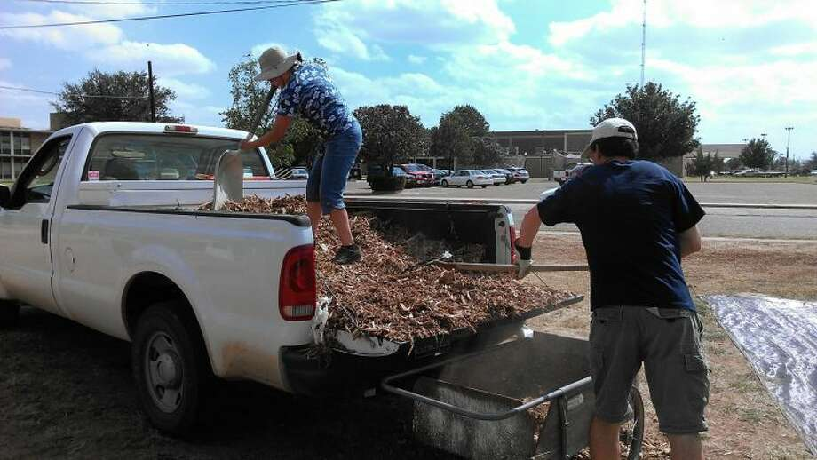 Courtesy Photo/Lynette BowenStacey Ontai and Peter Bowen unload mulch onto a wheelbarrow at the community garden at Eighth and Utica.