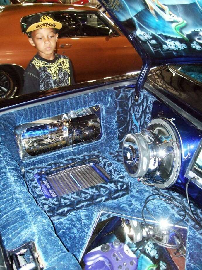 Eight-year-old Preston Stevenson of Plainview checks out the music system, hydraulics and gaming system in the trunk of a 1977 Chevy Monte Carlo owned by Lupe Palacio of Lubbock. The car was on display at the Ollie Liner Center on Saturday during a car show hosted by Wal-Mart Transportation benefitting the Children's Miracle Network.