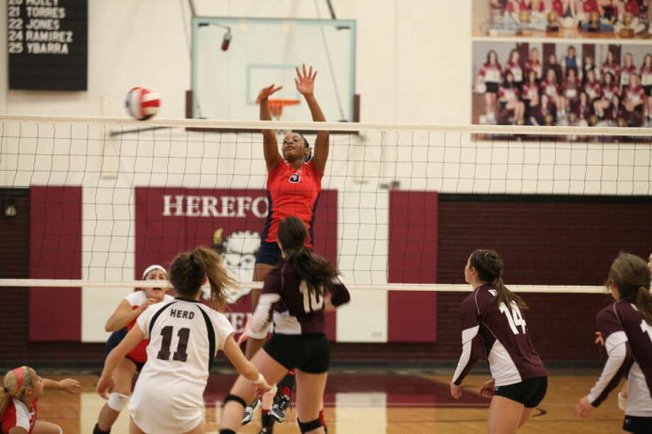 Plainview's Taivia Hearn (5) rises above the net attempting to block a Hereford hit during a District 4-4A volleyball match in Hereford Tuesday night. Photo: Photo Courtesy Of Bryan Hedrick/hererfordisd.net