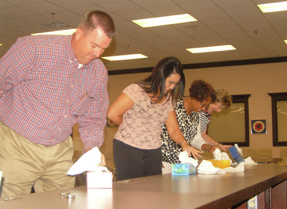 A contest to see how quickly participants could empty a box of tissues using only their left hands livened up Thursday's Plainview Area United Way's first report meeting. Kevin Carter (left) ended up winning the contest and the right to wear a blue first place ribbon. Other participants were Carmen Ortega, Sherrie Wall and Deana Sagesar. Photo: Doug McDonough/Plainview Herald