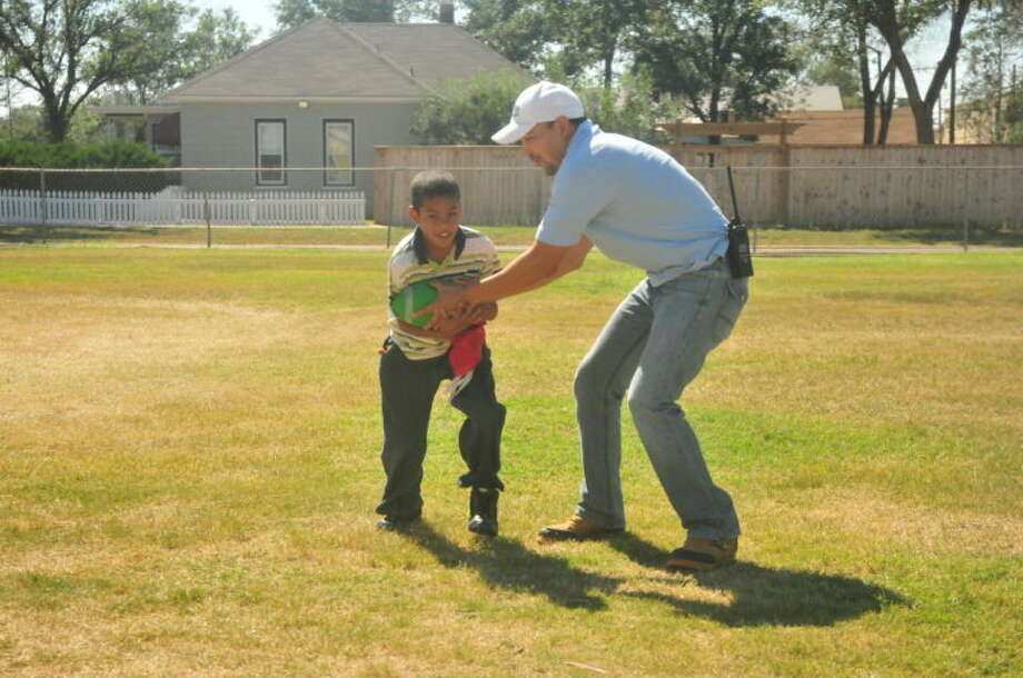 "Plainview Police Detective Robert Gallardo hands off the ball to Kabron Lewis during recess at Highland Elementary. Gallardo is one of the five detectives involved with the Big Brother Big Sister ""Lunch Buddy"" program. Photo: Homer Marquez/Plainview Herald"