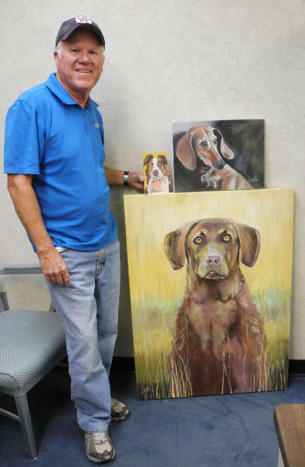 "David Leake of Lubbock paints commissioned dog portraits as a way to give back to the organization that helped him as he was growing up. Here he is shown with ""Big Boy,"" ""Dogie"" and ""Show Dog."" Photo: Gail M. Williams 