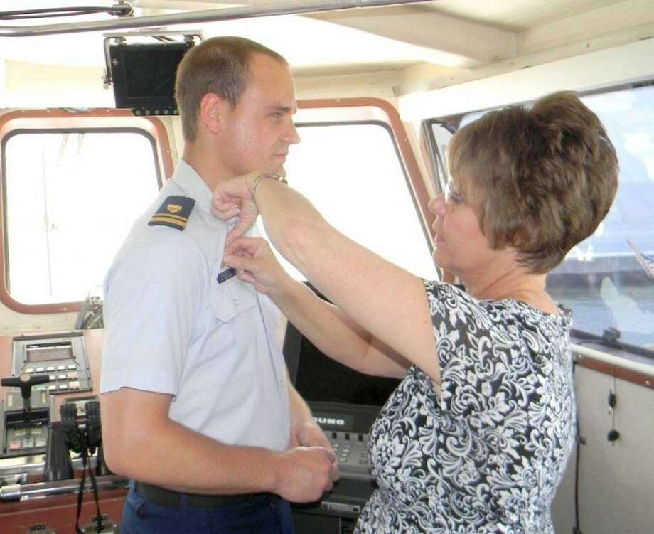 Donna Isaacson pins the command at sea insignia on the uniform of her son, Cody, the new captain of the Manowar.