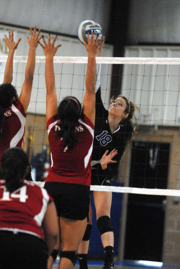 Laura Beth Earhart (18) hits the ball over two Christ The King blockers during Plainview Christian Academy's volleyball match Saturday. Photo: Skip Leon/Plainview Herald