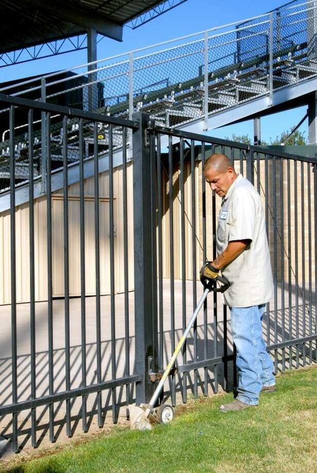 Wayland Baptist University employee Frankie Medina trims grass this morning along a railing at Wilder Field, which will play host beginning Friday to 10 teams participating in the Southwest Regional Baseball Tournament for 15 year olds. Most local motels are nearing capacity as fans began arriving Wednesday evening and this morning. Photo: Richard Porter/Plainview Herald
