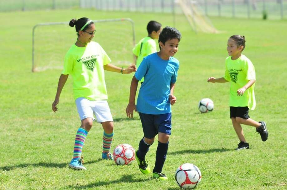 Seth Anthony Miranda (center) works on dribbling with fellow YMCA campers Catherine Delgado (left) and Daisy Maciel (right). Photo: Homer Marquez/Plainview Herald