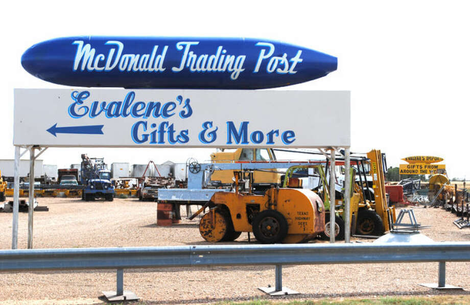 Ryan Crowe/Plainview HeraldA drop tank sits atop a steel and aluminum platform along Business I-27, advertising for McDonald Trading Post. A second tank, advertising Evalene's Imports, can be seen in the distance.