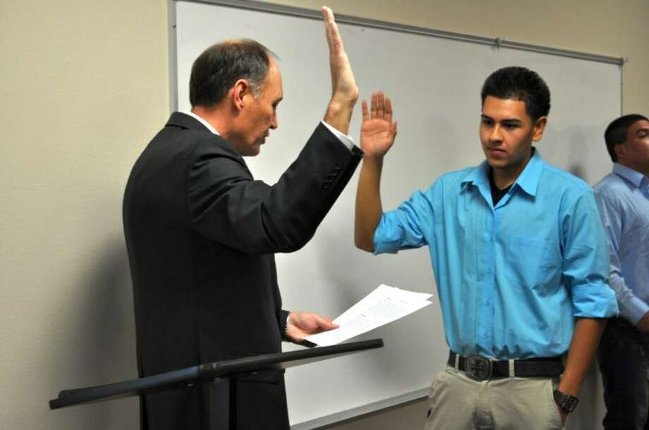 Courtesy photosSteven Guillen (right), new Houston School student council president, is sworn in by 64th District Judge Rob Kinkaid. The swearing in ceremony was part of a recent parent meeting/Hispanic Heritage month potluck dinner at the campus. The newly formed student council will coordinate community service projects and take an active role in the monthly parent meetings.