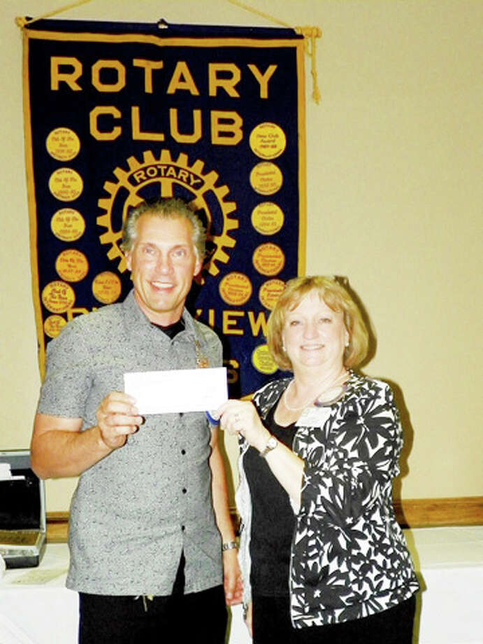 Ted Baker of Wal-Mart Transportation presents a $2,500 check to Rotarian Coralyn Dillard to help fund the Plainview Rotary Club's distribution of dictionaries to Hale County third graders.