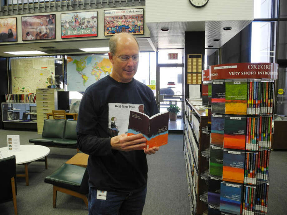 One of Unger Memorial Library's features is a series of short books which provide information about everything from philosophy to mechanics. Here, Head Librarian John Sigwald holds a book about robotics. Photo: Gail M. Williams | Plainview Herald