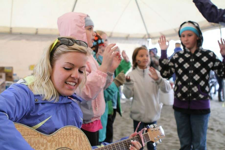 Wayland student Jennifer Rowell of Plainview plays the guitar as the Wayland mission team, including Hannah Brown (right), leads a song for children during their mission trip to Kenai, Alaska. Photo: Katie Trimble