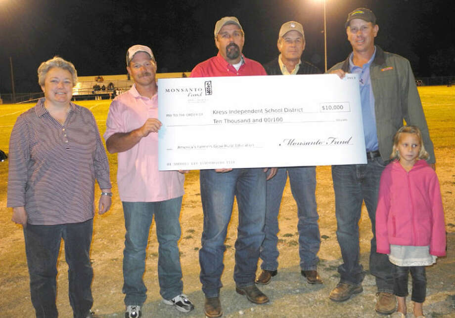 Gail Williams/Plainview HeraldKress Principal Leah Zeigler (left) and local farmers Cody Gruhlkey, Darren Tye and Kent Springer accept a $10,000 check from Monsanto representative Kirk Marnell and his daughter. Kress ISD received the $10,000 to benefit its math/science program.