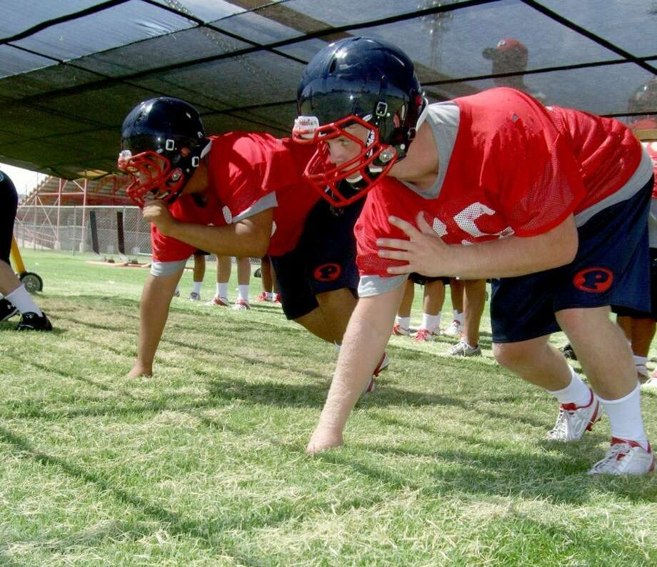 "Seniors Andrew Dunlap (right) and Danny Montelongo line up under a blocking device designed to help players stay low during the first day of two-a-day practices for the Plainview Bulldog football team on Monday. Practices for volleyball and band also got started Monday. The Red Rage Booster Club will meet at 11 a.m. Saturday following ""Bulldog Alley."" Their annual cookout will be from 11 a.m.-2 p.m. Aug. 13 in conjunction with the Bulldogs' freshman, JV and varsity scrimmages against Perryton."