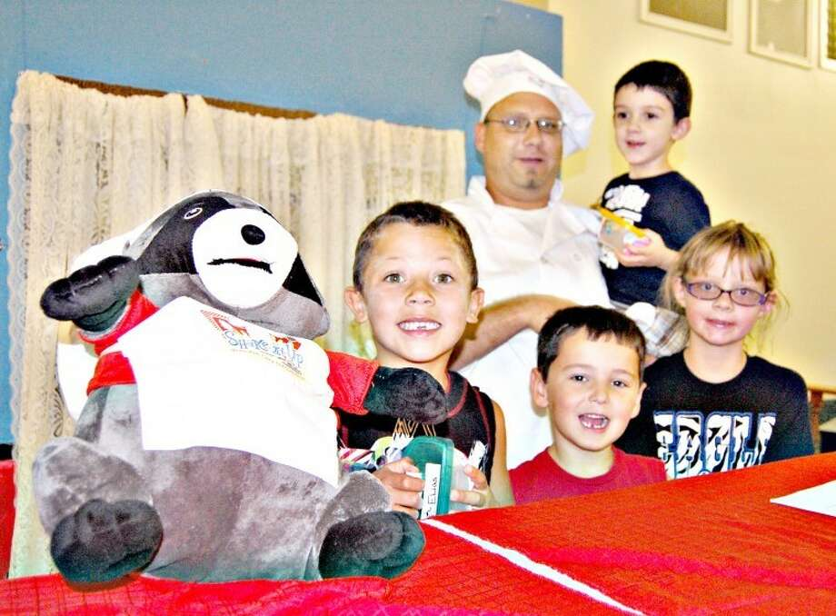Doug McDonough/Plainview HeraldA hand puppet named Scraps and Chef Basil (Jamey Qualls) welcome Elias Ramos (left), Zane Barton, Canalee Isom and Jerimiah Britto (held by Chef Basil) into the kitchen of the Shake It Up Cafe during Vacation Bible School at Seth Ward Baptist Church. Fifty-seven children have registered for VBS, which began Monday and runs from 6:30-8:30 p.m. daily through Friday. Activities include creative crafts, mission work, food science and music.