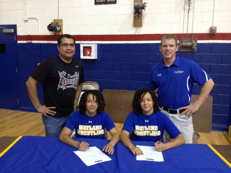 Genesis (left) and Abril Ramirez of El Paso sign agreements to compete in wrestling at Wayland Baptist University. Also pictured are El Paso El Dorado Wrestling Coach Freddy Flores (left) and Wayland Assistant Wrestling Coach Aaron Meister. Photo: Courtesy Photo