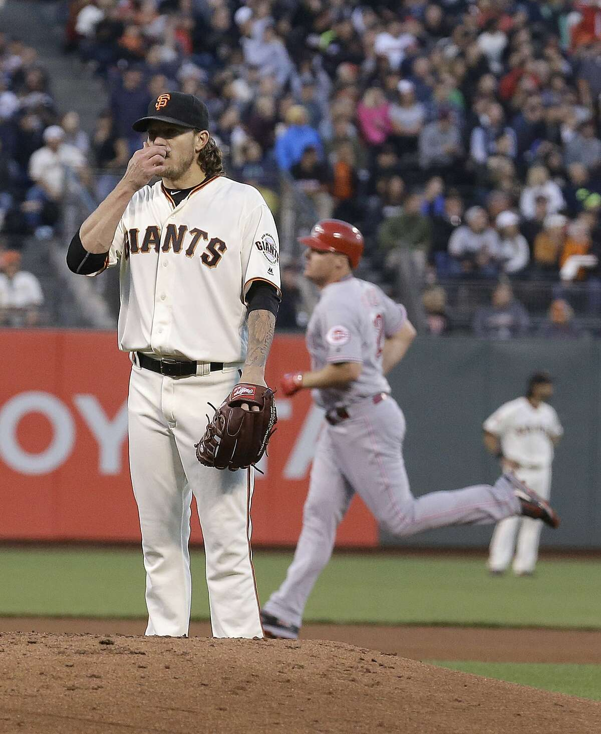 San Francisco Giants pitcher Jake Peavy, left, reacts after allowing a two-run home run to Cincinnati Reds' Jay Bruce, right, during the fourth inning of a baseball game in San Francisco, Monday, July 25, 2016. (AP Photo/Jeff Chiu)