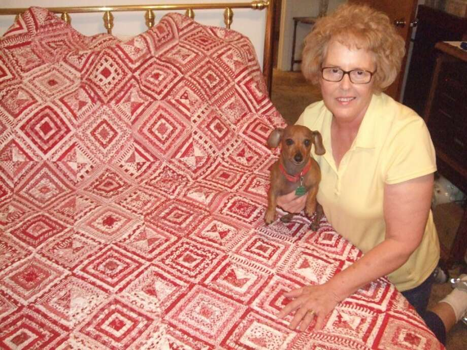 Jean Olson displays her masterpiece quilt she's worked on for nearly a year as Maggie enjoys its comfort. Her dachshund sat on her lap all year while she stitched. Photo: Shanna Sissom/Plainview Herald