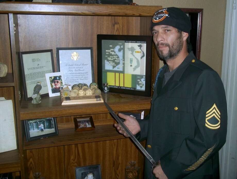 David Cornett poses with war memorabilia left by his late father, Larry Cornett. Photo: By JOSH WEST For The Herald