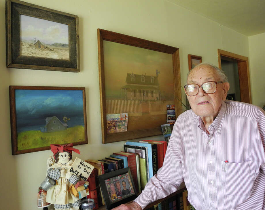 Hale Center resident Jack Smith stands in front of some of his paintings. At age 100, Smith still lives in his own home, attends church and goes to the senior citizen center. Photo: Gail M. Williams | Plainview Herald