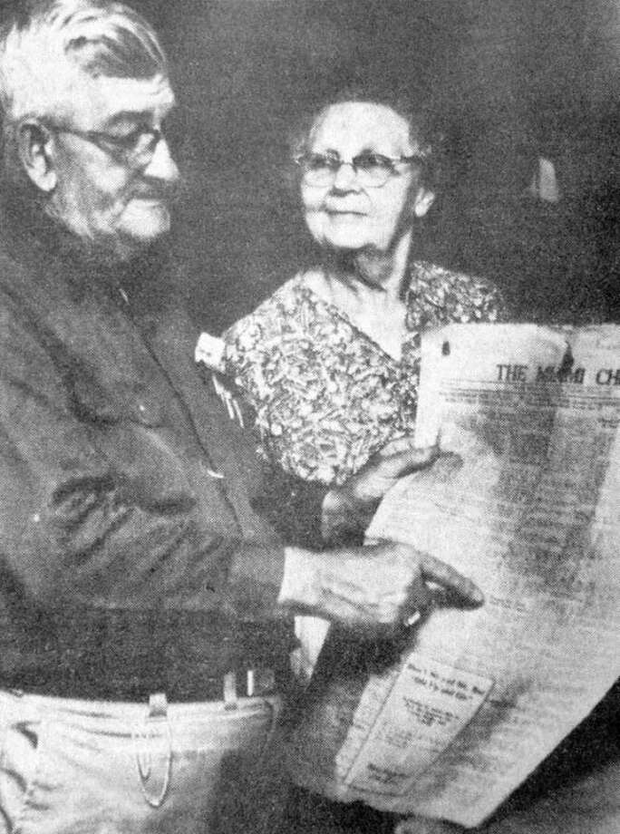 Mr. and Mrs. Earl W. Tallet are shown in 1972 reading an article in the Miami Chief from 1929, describing a damaging tornado that killed two northwest of Plainview.