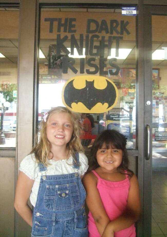 "Sisters Courtney and Hailee Fisher smile outside Cinemark Town Centre on Saturday just before going inside to see ""Dark Knight Rises"" with family members. While moviegoers expressed sadness over the massacre at a Colorado movie theater during the show opener, they are resolved not to be fearful."