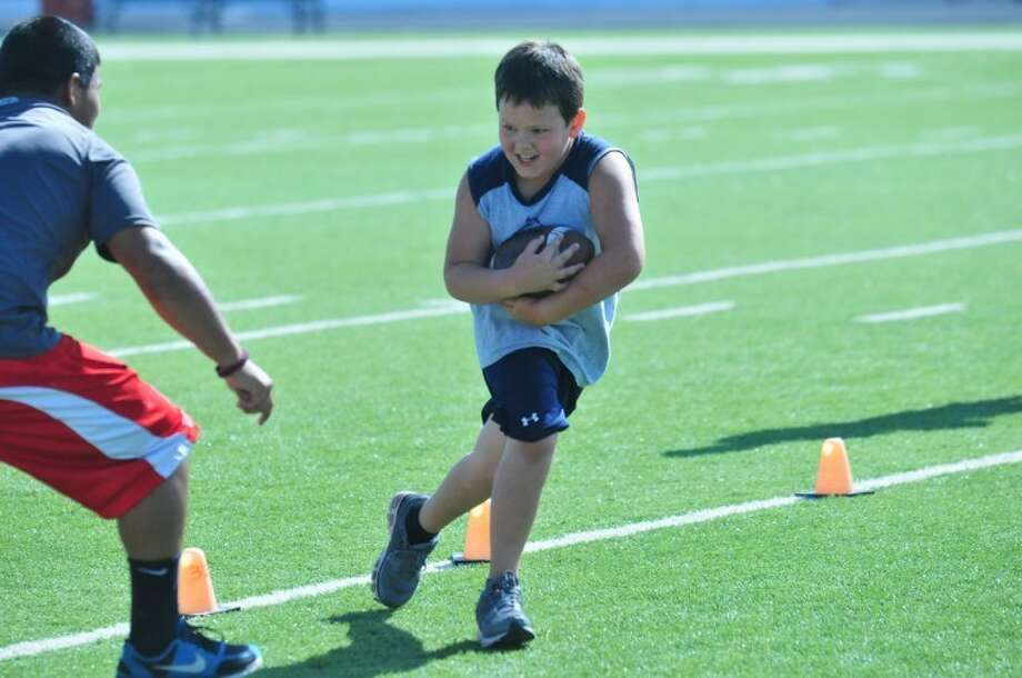 Austin Williams makes a dash with the football to pass a defender during the first day of drills at the 2012 Plainview Bulldog Camp of Champions. Photo: Homer Marquez/Plainview Herald