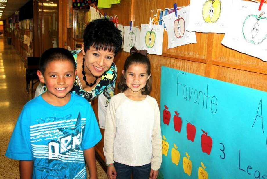 Photo By Jan Seago / Plainview ISDEdgemere Assistant Principal Angie Valdez's grandchildren, Izik Delgado and Sophi Valdez, are following in her footsteps. They are current students at Edgemere. Angie entered first grade at the campus when it opened in 1963. She remembers being a quiet child who was placed in a bilingual classroom and then moved a few weeks later to a regular classroom when the teacher realized she was fluent in English. Angie remembers Principal Reese Masten as a kind man and says that one of her favorite memories is walking to her teacher Mrs. Morris's house near the campus for a class picnic.