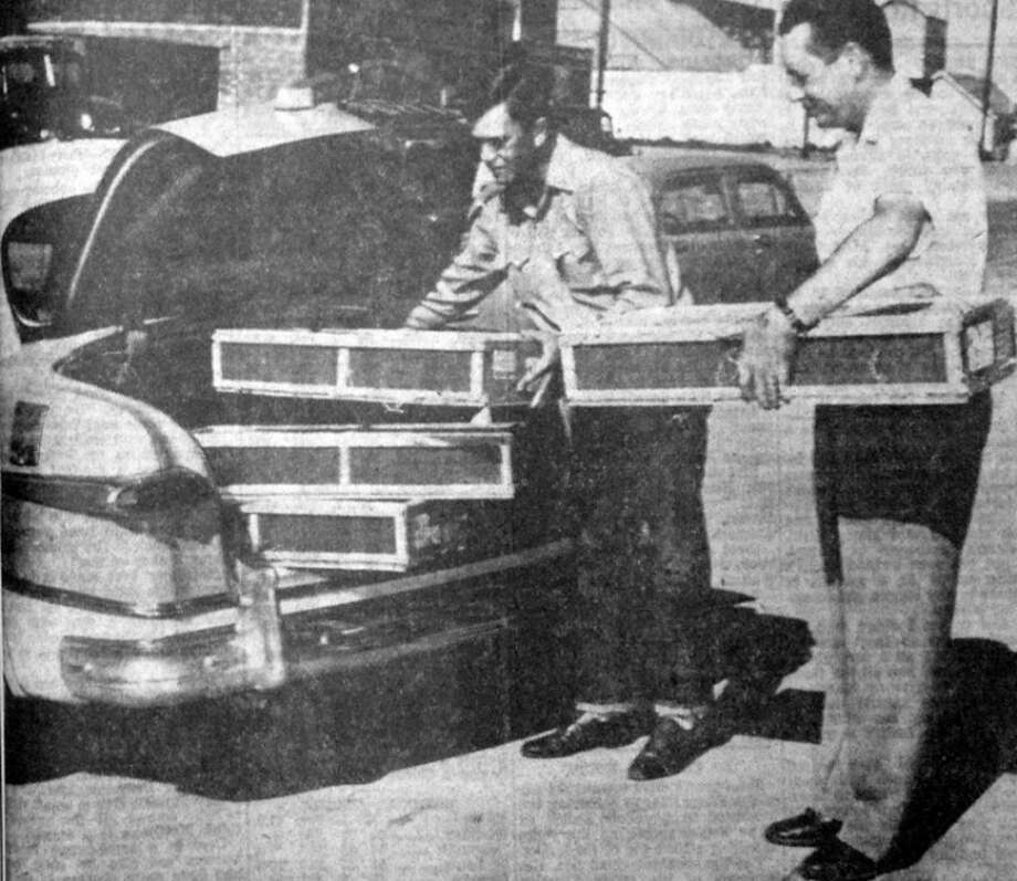 Virgil Rowland (right) of Rowland & Gordon Co., helps Richard Mott of Anton load crates containing approximately 520,000 ladybugs. In 1952 the local farm supply store sold the ladybugs by the gallon crate — each containing about 130,000 insects — for producers to use in their fight against plant lice and other pests. Photo: Herald File Photo