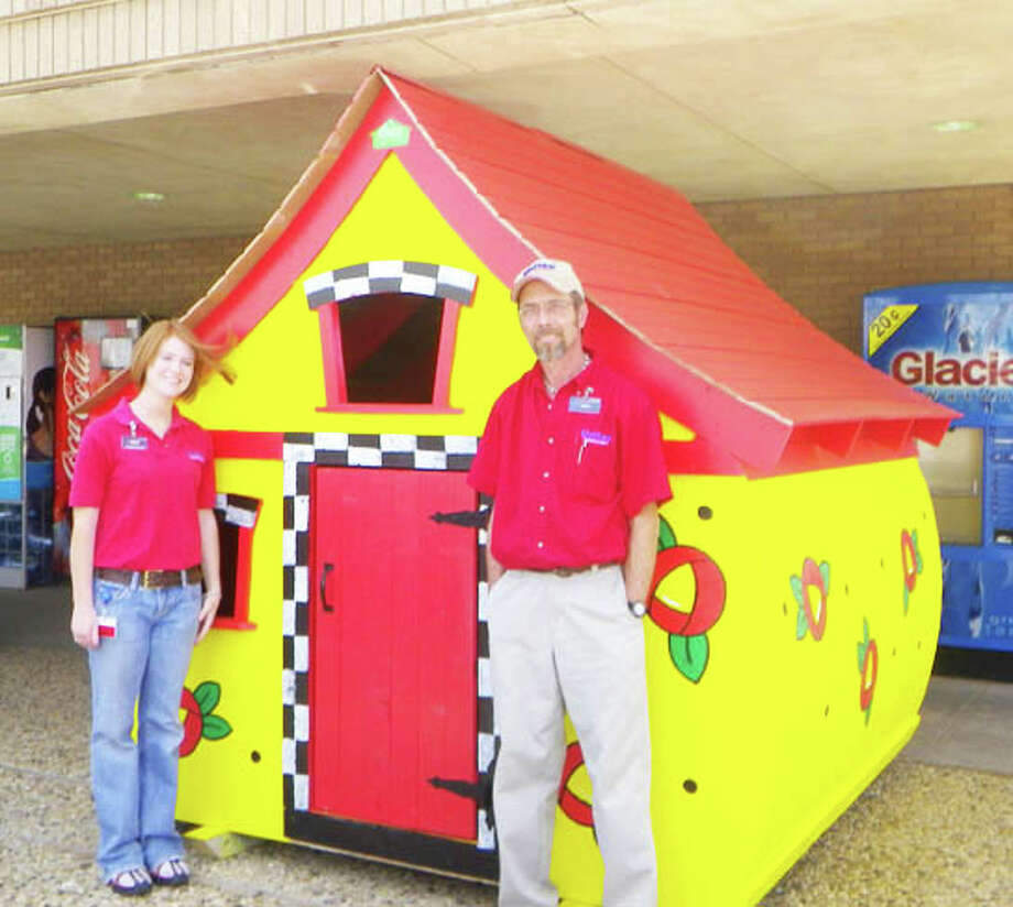 United Supermarket employees Haley Cochran and Jimmy Blackwell inspect a playhouse on display at the Olton Road store. The playhouse is one of six being raffled by CASA of the South Plains to benefit abused and neglected children.
